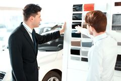 Handsome young man in dealership. Black is perfect. Rear view of a handsome business men and sales assistant choosing the color of the new car by the colour royalty free stock image