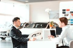 Handsome young man in dealership Stock Images