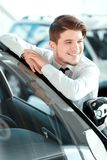 Handsome young man in dealership Royalty Free Stock Photography