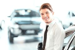 Handsome young man in dealership Royalty Free Stock Image