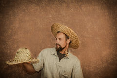 Handsome young man demonstrate fashionable straw hats Royalty Free Stock Photos