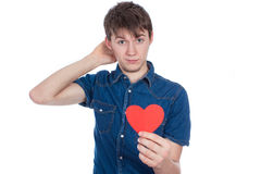 Handsome young man in denim blue shirt standing on a white background with a red paper heart in hands. Stock Photos