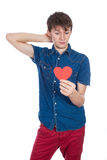 Handsome young man in denim blue shirt standing on a white background with a red paper heart in hands. Royalty Free Stock Photo