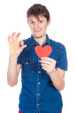 Handsome young man in denim blue shirt standing on a white background with a red paper heart in hands. Stock Photography