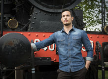 Handsome young man in denim shirt in front of old train Royalty Free Stock Photos