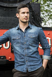 Handsome young man in denim shirt in front of old train Stock Photos