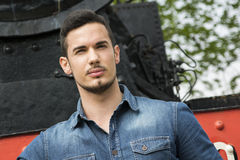 Handsome young man in denim shirt in front of old train Stock Photography