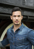 Handsome young man in denim shirt in front of old train stock image