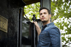 Handsome young man in denim shirt hanging from old train Royalty Free Stock Photos