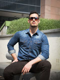 Handsome young man with denim shirt and sunglasses sitting Stock Photos