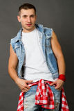 Handsome young man. In a denim vest on a gray background Stock Photography