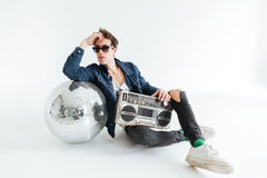 Handsome young man with disco ball and boombox. Image of handsome young man wearing sunglasses sitting  over white background with disco ball and boombox Stock Photos