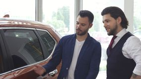 Two male friends discuaaing a new car at the dealership salon. Handsome young man discussing a new automobile for sale with his friend while shopping for a car stock video footage