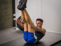 Handsome young man doing abs exercises on mat. Attractive muscular young man in gym working out, doing exercises for abs on the ground royalty free stock photography