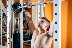 Handsome young man doing exercises in the gym. The concept of fitness, sports and a healthy lifestyle Stock Photography