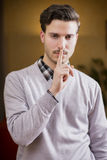 Handsome young man doing Hush sign with finger on lips Stock Photo