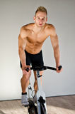 Handsome young man doing spinning on bike Royalty Free Stock Photo
