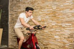 Handsome young man doing spinning on bike. Attractive young man exercising in gym: spinning on stationary bike Stock Photo
