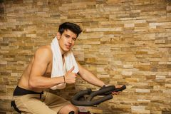 Handsome young man doing spinning on bike Stock Photo