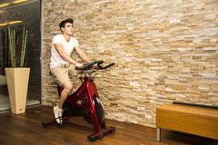 Handsome young man doing spinning on bike Stock Photos