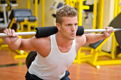 Handsome young man doing squats in gym Stock Images