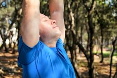 Handsome young man is doing stretching exercises in forest. Sportsman wearing sportswear in landscape nature outdoors. Pretty guy, active, cross fit, healthy Royalty Free Stock Photography