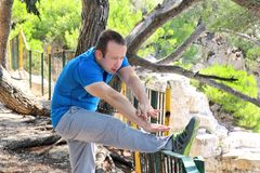 Handsome young man is doing stretching exercises in forest. Sportsman wearing sportswear in landscape nature outdoors. Pretty guy, active, cross fit, healthy Royalty Free Stock Photos