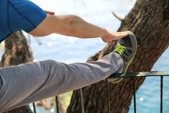 Handsome young man is doing stretching exercises in forest. Sportsman wearing sportswear in landscape nature outdoors. Stock Image