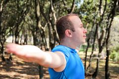 Handsome young man is doing stretching exercises in forest. Sportsman wearing sportswear in landscape nature outdoors. Pretty guy, active, cross fit, healthy Royalty Free Stock Photo