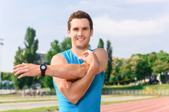 Handsome young man doing stretching Stock Images