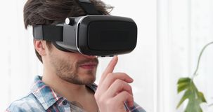 Handsome man using virtual reality simulator stock video footage