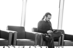 Handsome young man with dreadlocks using his digital tablet pc at an airport lounge, modern waiting room, with backlight.  stock image