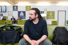 Handsome young man with dreadlocks. Waiting at an airport lounge stock photography