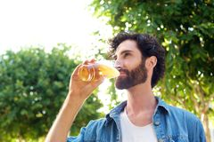 Handsome young man drinking beer outdoors Royalty Free Stock Photo
