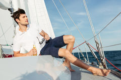 Handsome young man drinking beer while resting on the yacht Royalty Free Stock Image