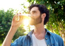 Handsome young man drinking beer in summer Stock Image