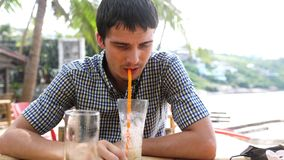 Handsome young man drinking cocktail in beach cafe sitting by sea. slow motion. 3840x2160 stock video