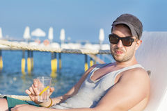 Handsome young man drinking cocktail on the beach Stock Photography
