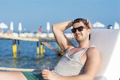 Handsome young man drinking cocktail on the beach Stock Photos