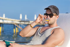 Handsome young man drinking cocktail on the beach Royalty Free Stock Photography