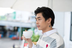 Handsome young man drinking coffee looking out at the view from Stock Images