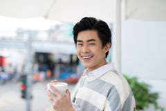 Handsome young man drinking coffee looking out at the view from Royalty Free Stock Photography