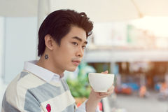 Handsome young man drinking coffee looking out at the view from Stock Photography
