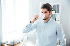 Handsome young man drinking coffee in office Stock Photography