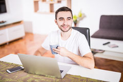 Handsome young man drinking coffee while working with laptop in kitchen. Handsome man drinking coffee while working with laptop in kitchen Stock Photography