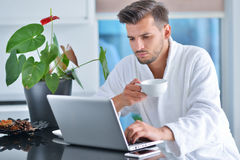 Handsome young man drinking coffee while working with laptop in kitchen Stock Photography