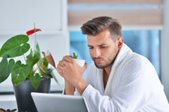 Handsome young man drinking coffee while working with laptop in kitchen.  Stock Photography