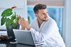 Handsome young man drinking coffee while working with laptop in kitchen.  Stock Photo