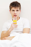 Handsome young man drinking juice Royalty Free Stock Photos