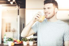 Man drinking orange juice Stock Photos